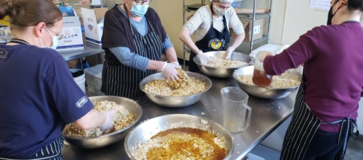 Golden Girl Granola bakers mixing ingredients