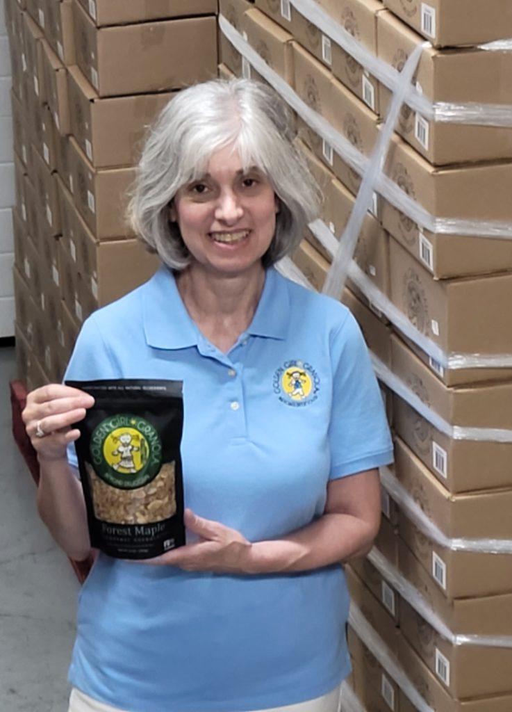 Deborah showing granola boxes